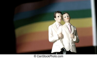 Gay groom cake toppers in front of rainbow flag moving in...