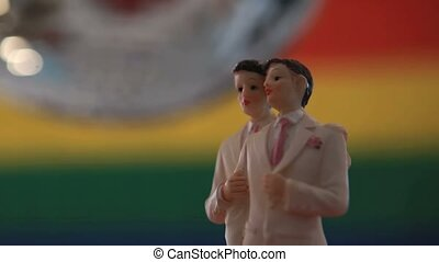 Gay groom cake toppers with disco ball in front of rainbow...