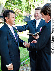 Gay Marriage Ceremony - Rings - Groom slips a ring on his...