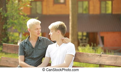 Gay men relaxing in the park. wooden house