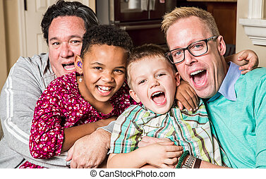 Gay parents pose with their childen in the living room