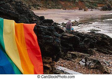 Gay pride flag on a sunset beach with a man in the background