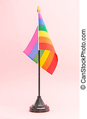 Gay Pride flag on stand on pink background