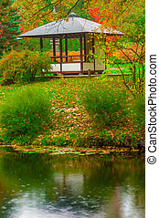 gazebo in the empty autumn park near the pond