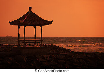 Gazebo on the ocean shore at sunset. Indonesia, Bali