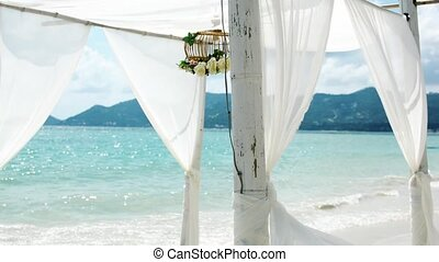 Gazebo with flowers on the beach. Wedding background -...