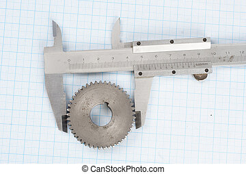 gear and caliper on  graph paper background