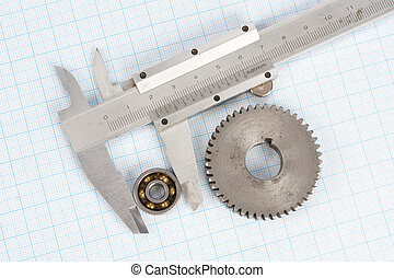 gear, bearing and caliper on  graph paper background