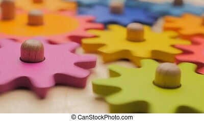 Gears and cogs macro in colorful wooden toy. Team work ...