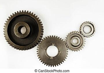 Gears - Four metal gears on plain background