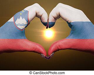 gebaar, gemaakt, door, slovenië vlag, gekleurde, handen, het tonen, symbool, van, hart, en, liefde, gedurende, zonopkomst