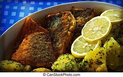 Gebackene Karpfenstücke mit Kartoffeln und Zitronenscheiben; fried pieces of carp with potatoes and lemon slices