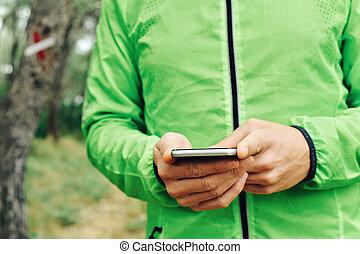 gebrauchend, seine, smartphone, junger, sportler