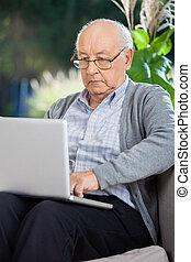 gebruikende laptop, man, senior, portiek