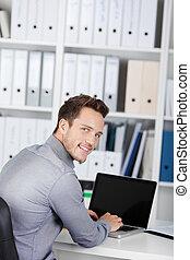 gebruikende laptop, zakenman, het glimlachen, bureau