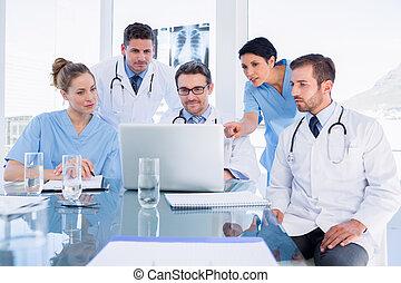 geconcentreerd, medisch team, gebruikende laptop, samen