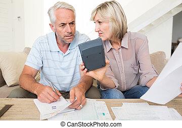 geconcentreerd, paar, middelbare leeftijd , thuis, rekeningen, rekenmachine