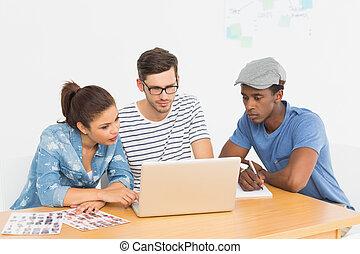 geconcentreerd, werkende , draagbare computer, drie, jonge, kunstenaars