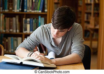 geconcentreerde, mannelijke student, werkende