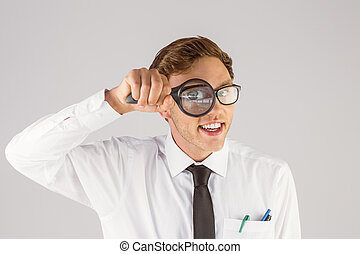 Geeky businessman looking through magnifying glass