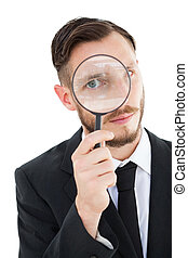 Geeky businessman looking through magnifying glass on white...