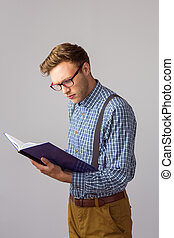 Geeky student reading a book on grey background
