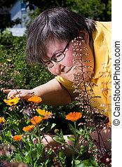 gehandicapte vrouw, sneeen, bloemen, in de tuin