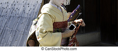 geisha girls - Geishas walking by an old street
