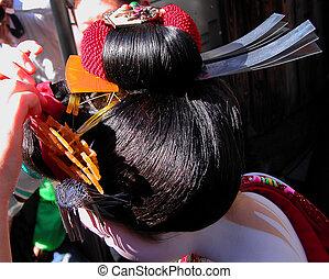 Geisha hairstyle - Two hands dressing a geisha's hair during...