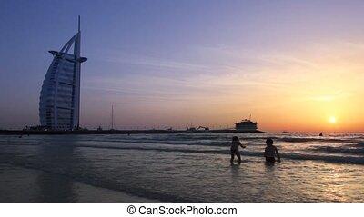 geitjes, op het strand, gedurende, ondergaande zon , dichtbij, de, burj al arabier, in, dubai