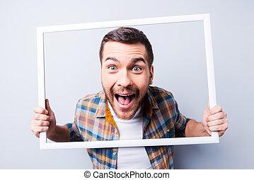 gek, picture., mooi, jonge man, in, hemd, vasthouden, fotolijst, voor, zijn, gezicht, en, het glimlachen, terwijl, staand, tegen, grijze , achtergrond