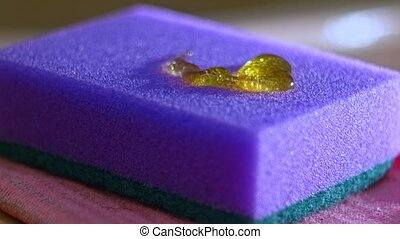 Gel for washing dishes of yellow color is poured on a blue...