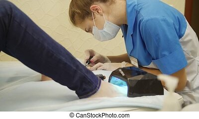 Gel pedicure in a cosmetology clinic. Specialist painting...