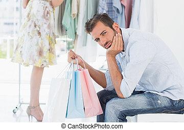 gelangweilte , mann, mit, einkaufstüten, während, frau, per,...