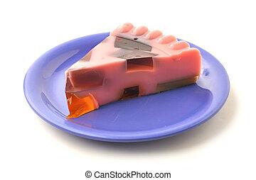 Gelatin - Beautiful slice of molded pink gelatin on blue...