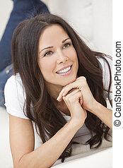 gelukkig glimlachen, mooie vrouw, het leggen op de sofa