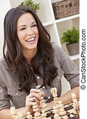 gelukkig glimlachen, mooie vrouw, spelend schaakspel