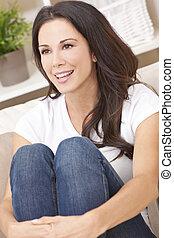 gelukkig glimlachen, mooie vrouw, zitten op sofa