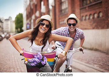 gelukkig paar, cycling, in de stad