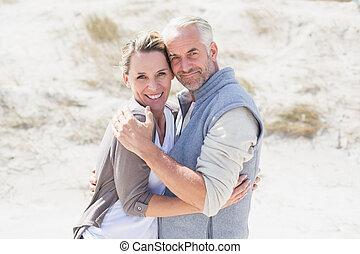 gelukkig paar, het koesteren, op het strand, kijken naar van fototoestel