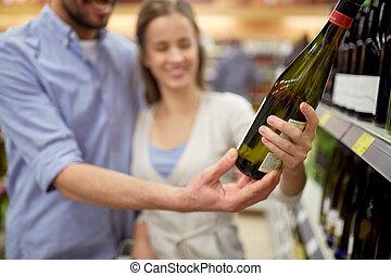 gelukkig paar, met, fles van wijn, op, drank opslag