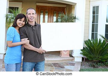 gelukkig paar, thuis, met, meldingsbord