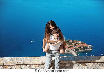 gelukkig paar, verliefd, zomer, vacations., jonge man, piggybacking, zijn, mooi, vriendin, op, zee, terwijl, lachen, op, camera., sveti, stefan, eiland, in, budva, montenegro