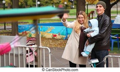 gelukkige familie, met, baby, stalletjes, in, vermakelijkheid park