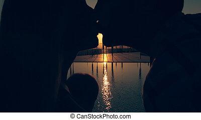 gelukkige familie, met, drie kinderen, bewonderen, de, ondergaande zon , weerspiegelde in, de, oppervlakte, van, de, pool
