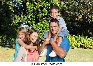 gelukkige familie, met, kinderen, op, hun, schouders