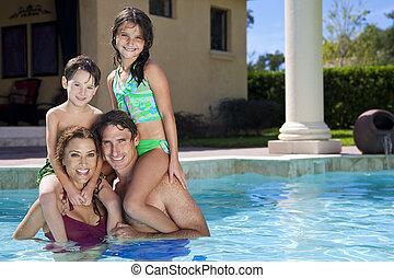 gelukkige familie, met, twee kinderen, spelend, in, een, zwembad