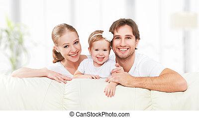 gelukkige familie, moeder, vader, kind, baby dochter, thuis, op, sofa, spelend, en, lachen