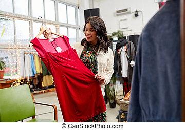 gelukkige vrouw, kies, jurkje, op, de opslag van de kleding