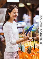 gelukkige vrouw, met, mand, en, tablet pc, in, markt